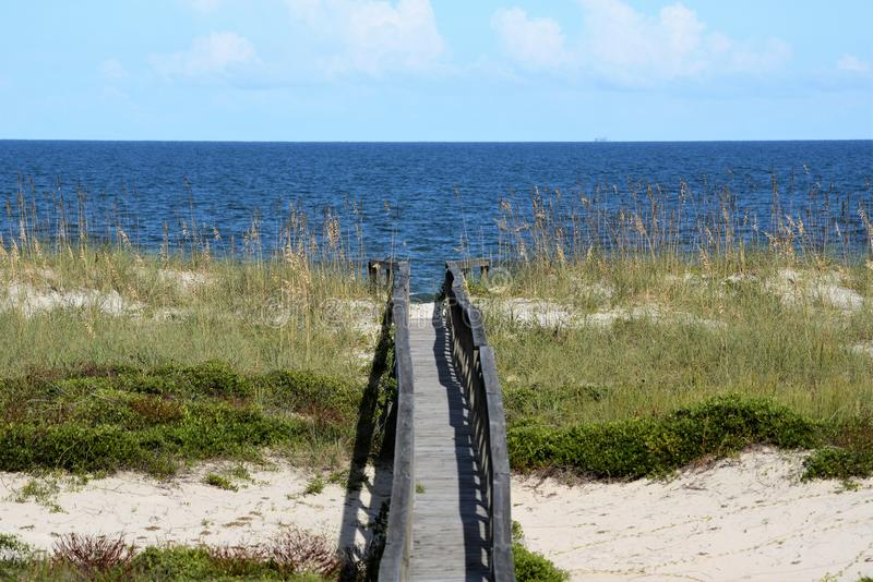 The long wood bridge allows for foot traffic over the sandy beach dune below. The dunes of the sandy beach protect the entire area from water and wind damage royalty free stock photography