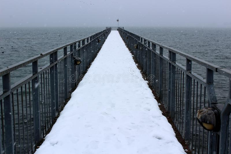 Long wood pier covered in snow reaches out over vast expanse of choppy water royalty free stock photography