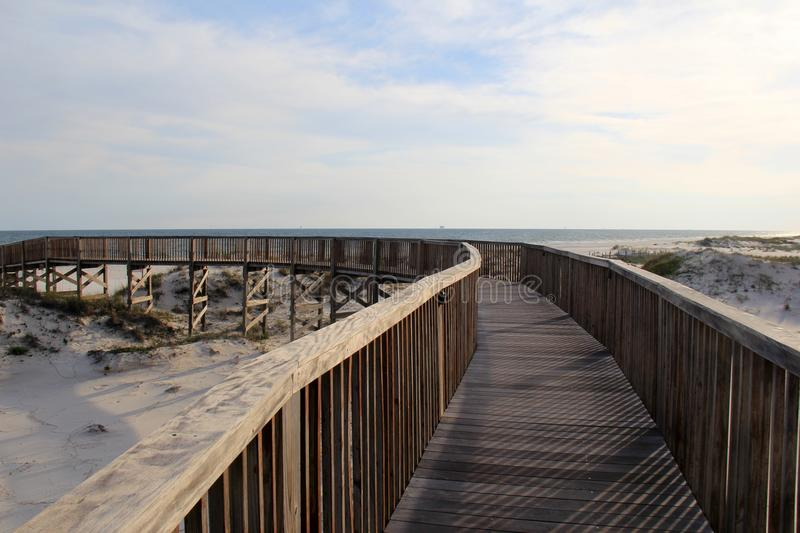 Long wood pier leading guests out to the sandy beach and ocean. Long curving wood pier leading beach goer`s out to the sandy shores and ocean waters just beyond royalty free stock image