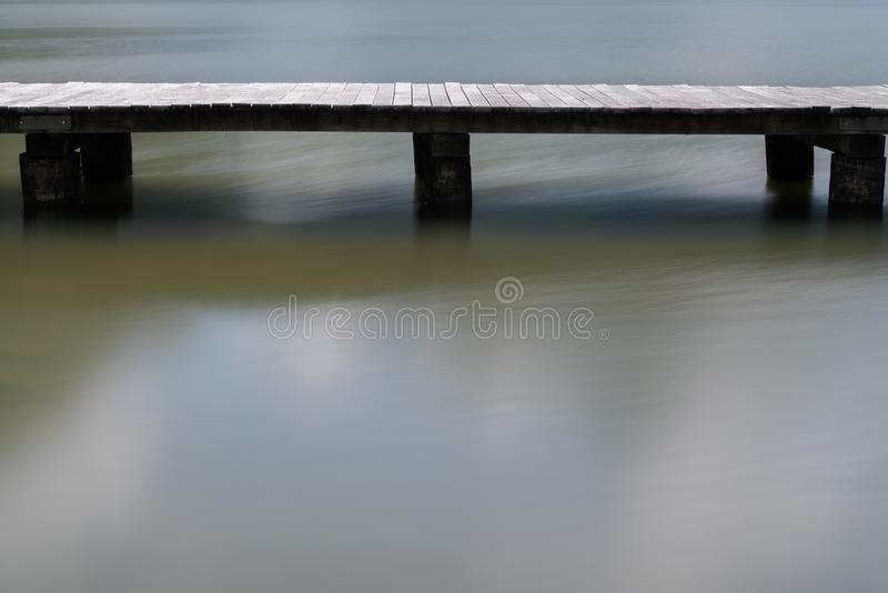 Long wooden boardwalk on a calm and placid mountain lake abstract view with copy space royalty free stock photo