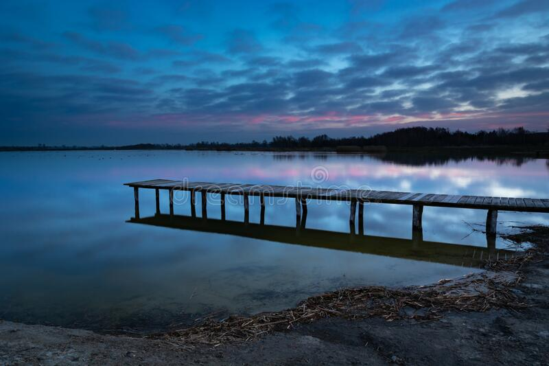 A long wooden bridge towards the water, evening blue and pink clouds after sunset in Staw, Poland royalty free stock images
