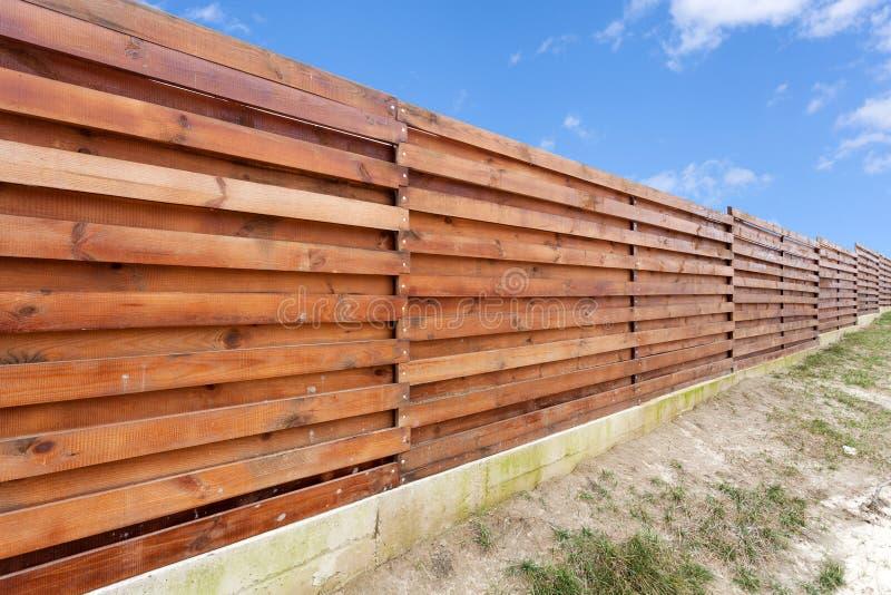 Long wooden cedar fence against blue sky. stock photography