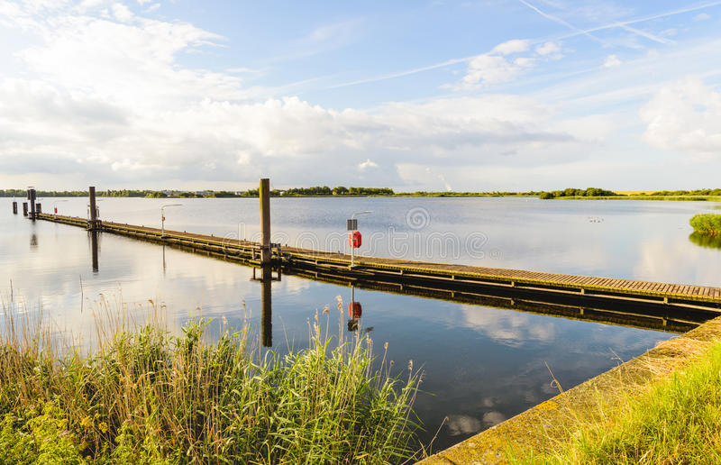 Long wooden jetty in a lake with a mirror smooth surface. Long wooden jetty in a lake with a mirror smooth water surface and diagonally into the image. It is royalty free stock photos