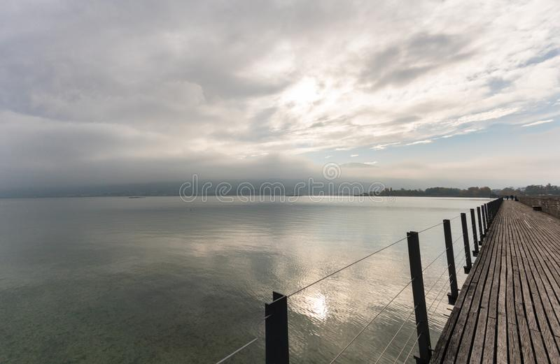 Long wooden boardwalk pier over water with a mountain landscape under an overcast sky royalty free stock photo