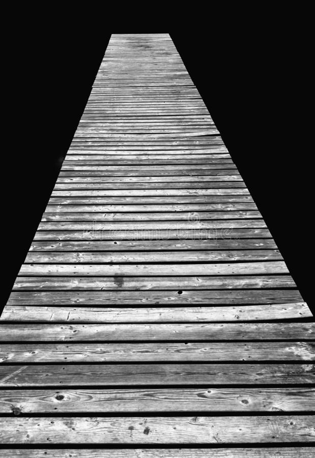 Long wooden pier leads out into dark black peat lake water royalty free stock photo