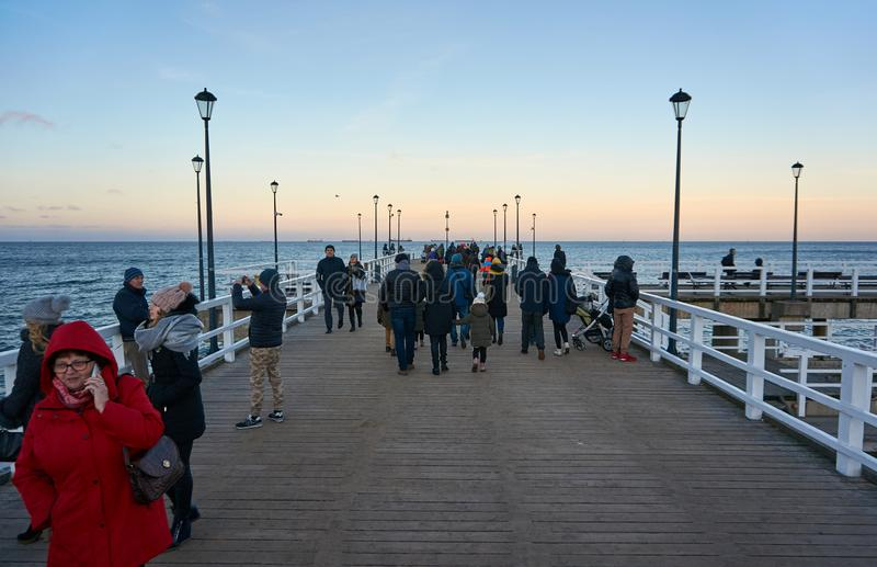 Long wooden pier into the sea with people on it stock photos