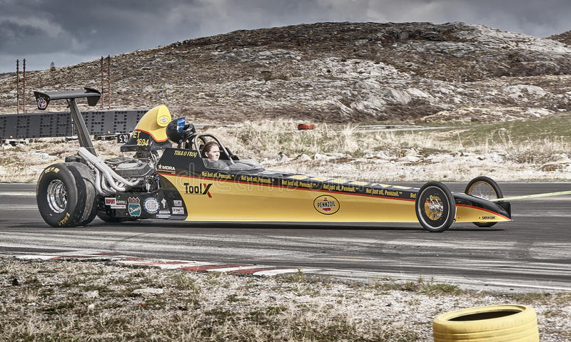 Long yellow race car with driver stock photography