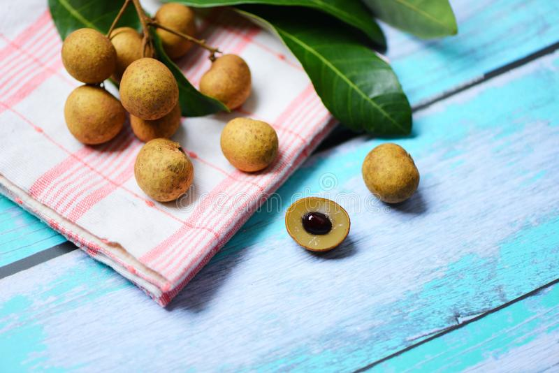 Longan fresh tropical fruit and green leaf in Thailand / Dimocarpus longan and peel exotic fruits on white wooden stock photography