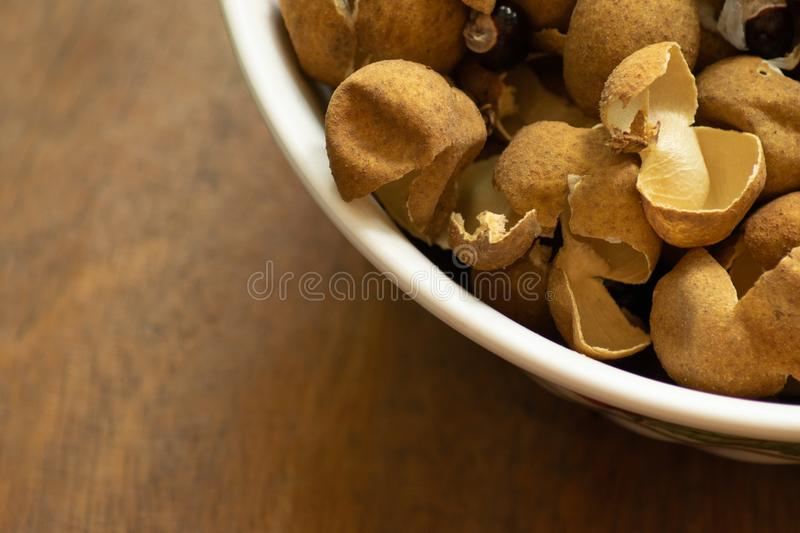 Longan peel in a bowl on wood background stock photos