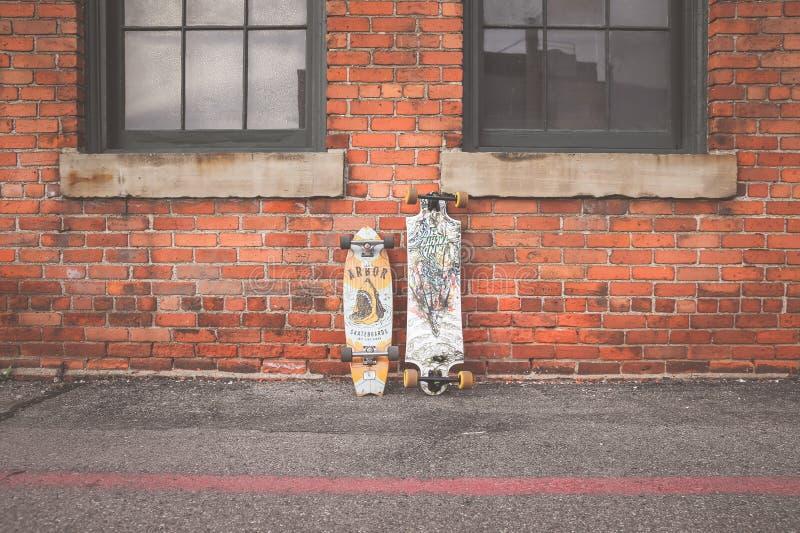 两白色和布朗倾斜在布朗砖墙的Longboard 免版税库存照片