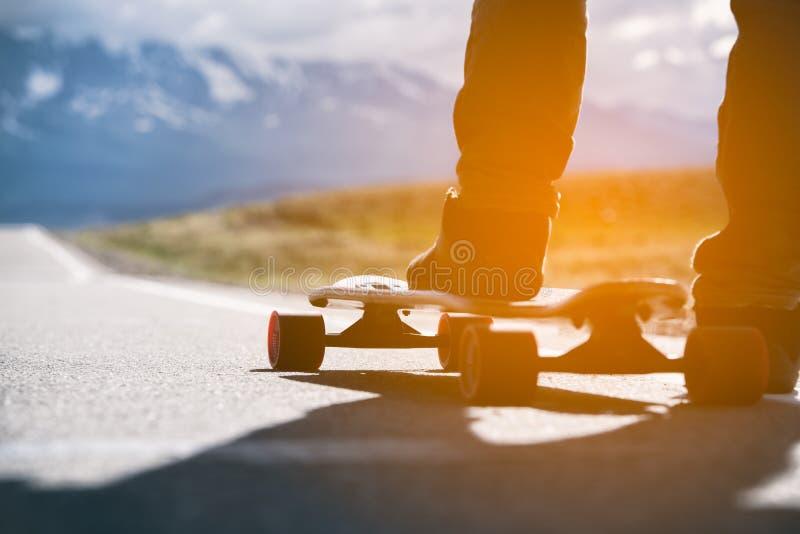 Longboard con el athlete& x27; el pie de s está en el camino en las montañas Luz del sol fotos de archivo