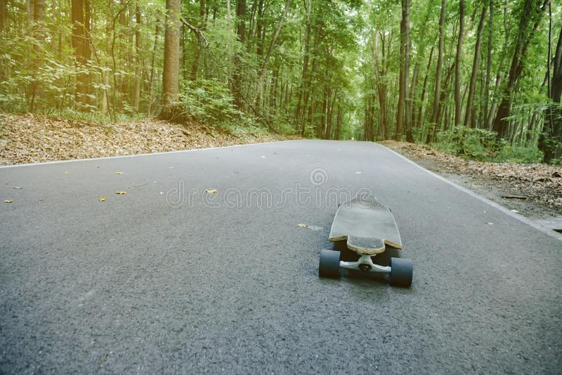 Longboard on the road in the woods Longboard outdoors. Forest, close, uo, fall, leaves, outside, skateboard, landscape, nature, travel, wallpaper, account royalty free stock images