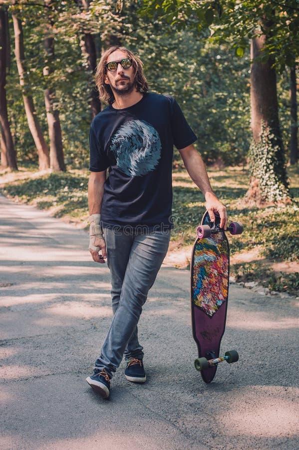 Longboard som åker skridskor - en longboarder som poserar bredvid hans longboard fotografering för bildbyråer