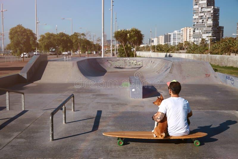 Longboarder в парке конька с его собакой стоковое фото rf