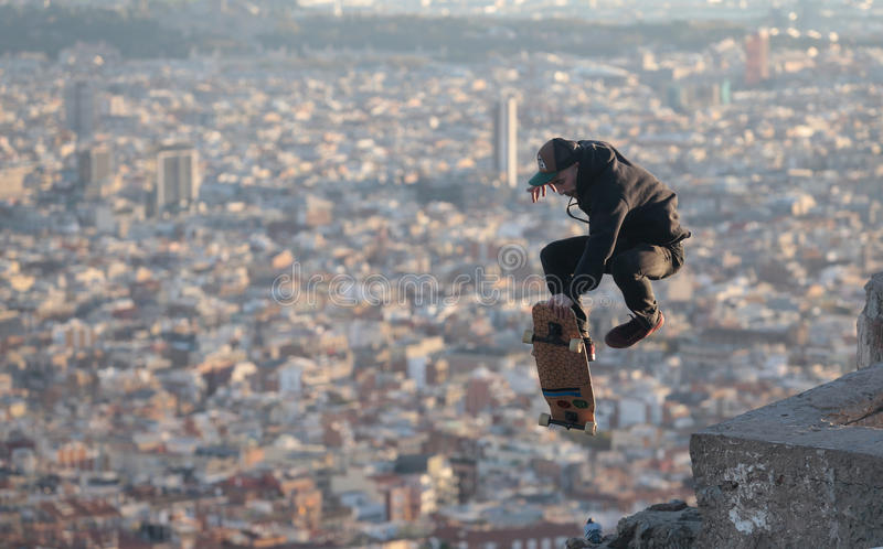 Longboarder fly and tricks over barcelona. A man jumps while skating on his longboard during a local tricks competition in Barcelona, view from nearby hill of stock photos
