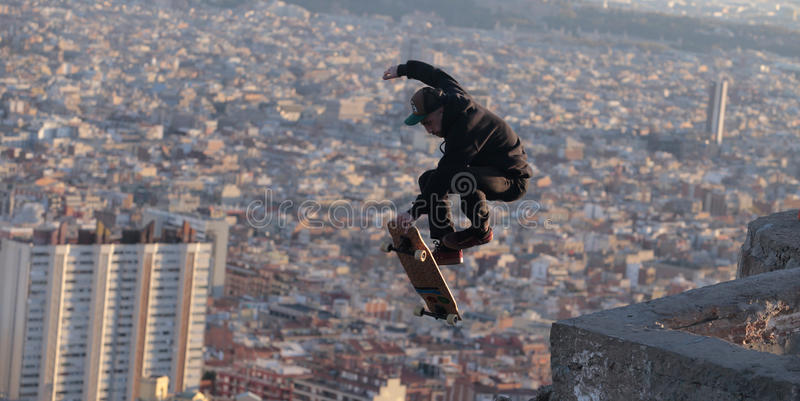 Longboarder flying over barcelona. A man jumps while skating on his longboard during a local tricks competition in Barcelona, view from nearby hill of Turo de la royalty free stock photography