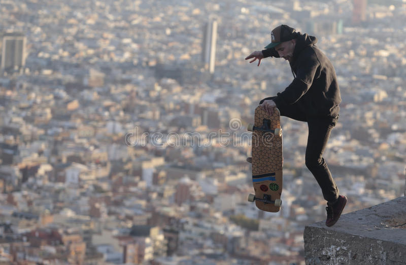 Longboarder jumps over barcelona. A man jumps while skating on his longboard during a local tricks competition in Barcelona, view from nearby hill of Turo de la royalty free stock photos