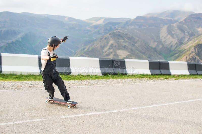 Longboarder no longboard no capacete e nas luvas dos macacões executar uma corrediça de pé na velocidade quando em uma estrada da fotografia de stock royalty free