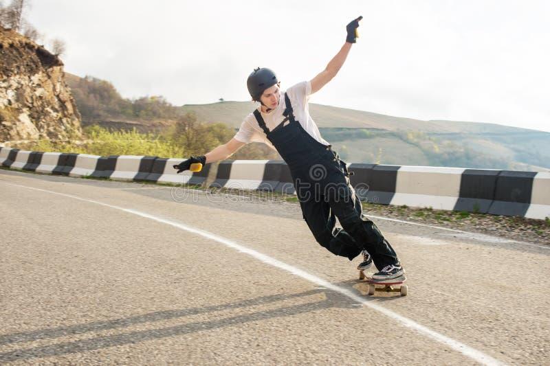 Longboarder no longboard no capacete e nas luvas dos macacões executar uma corrediça de pé na velocidade quando em uma estrada da imagem de stock royalty free