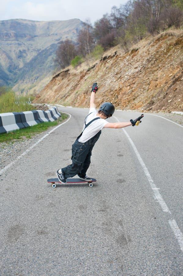 Longboarder no longboard no capacete e nas luvas dos macacões executar uma corrediça de pé na velocidade quando em uma estrada da fotografia de stock