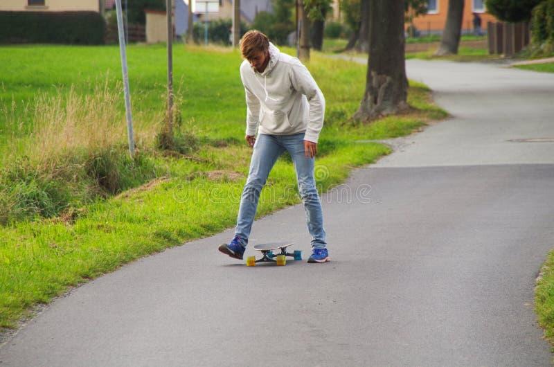 Longboarder på gatan som får baksida på bräde arkivfoto