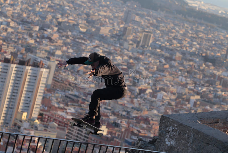 Longboarder trick over barcelona. A man jumps while skating on his longboard during a local tricks competition in Barcelona, view from nearby hill of Turo de la stock images