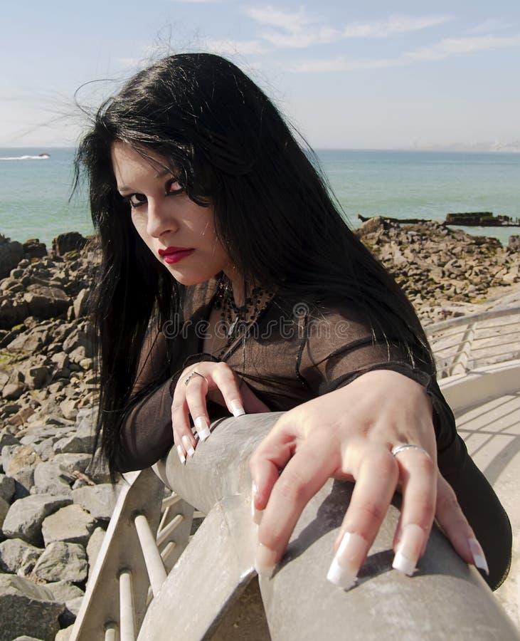 Longed nailed woman at seaside. Gothic young woman posing outdoors at the seacoast of Valparaiso royalty free stock photography