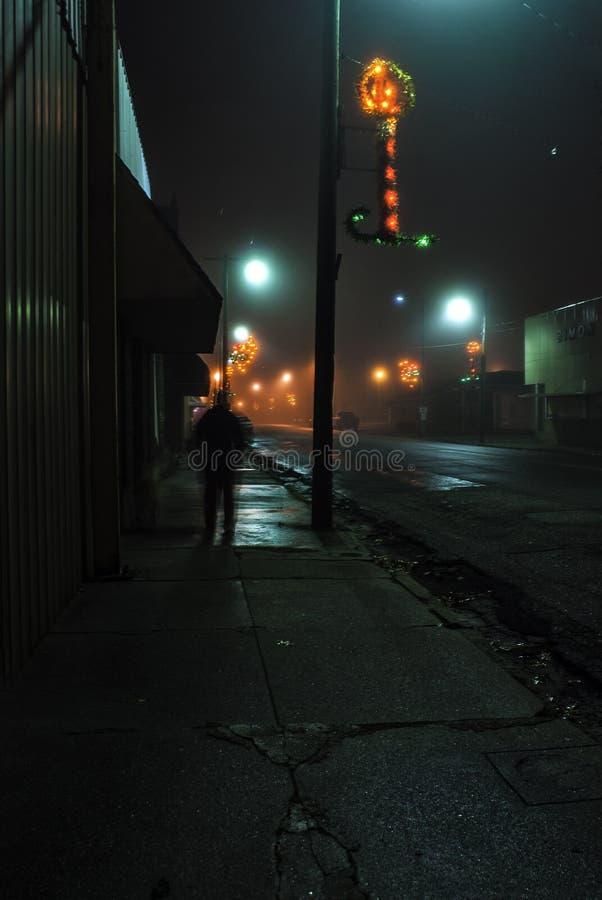 Longely uma figura em uma noite nevoenta no Weir do centro, Kansas durante o tempo do Natal imagens de stock