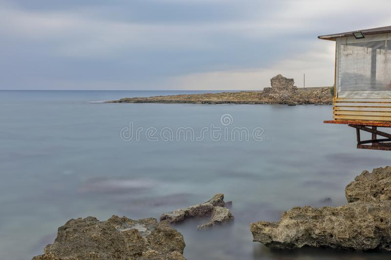 Longexposure sea side. Long exposure in Antalya, with brown rocky seaside and cloudy weather. Longexposure time 4 minutes stock image