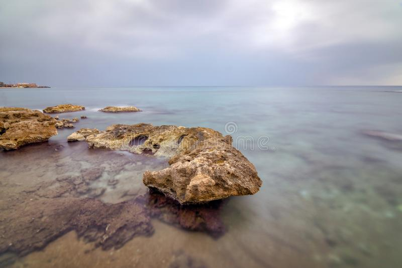 Longexposure sea side. Long exposure in Antalya, with brown rocky seaside and cloudy weather. Longexposure time 4 minutes royalty free stock photos