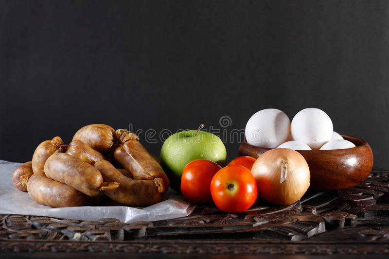 Longganisa Breakfast. Ingredients for breakfast of eggs and sausages from Imus, Cavite, Philippines with apple for dessert royalty free stock photography
