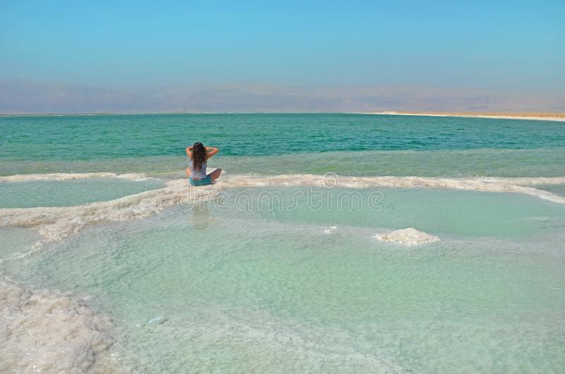 Longhaired brunette woman sitting on salt. water surface of Dead Sea in Israel with view of mountain Jordan. Merging with nature. Long-haired brunette woman royalty free stock photography