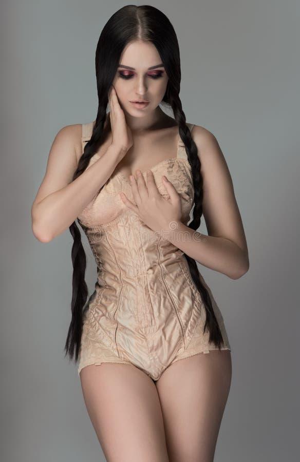Longhaired girl in beige bodysuit stock image