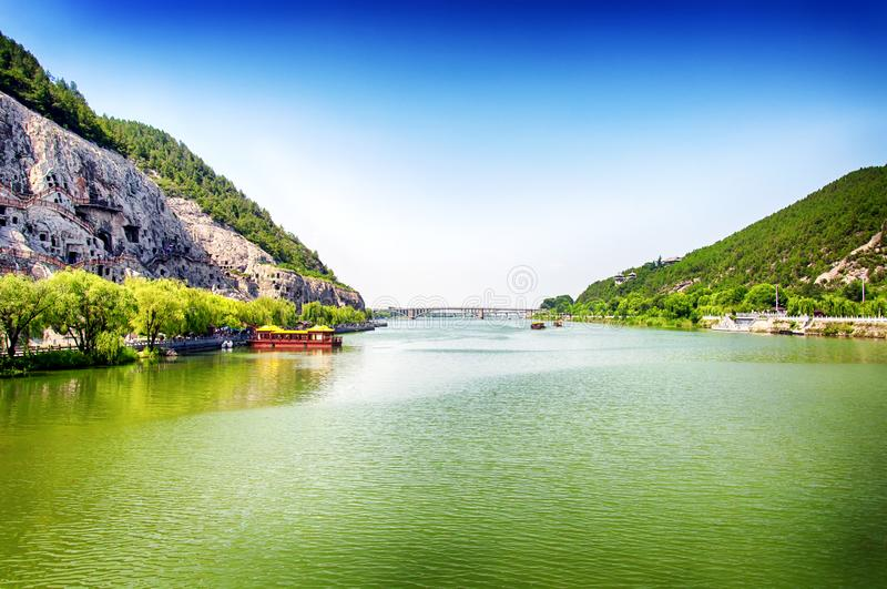Longmen grottoes scenic area and Yi River Luoyang China. The Yi River flanked by Longmen Grottoes and the Longmen Bridge in the distance in Luoyang China in royalty free stock photos