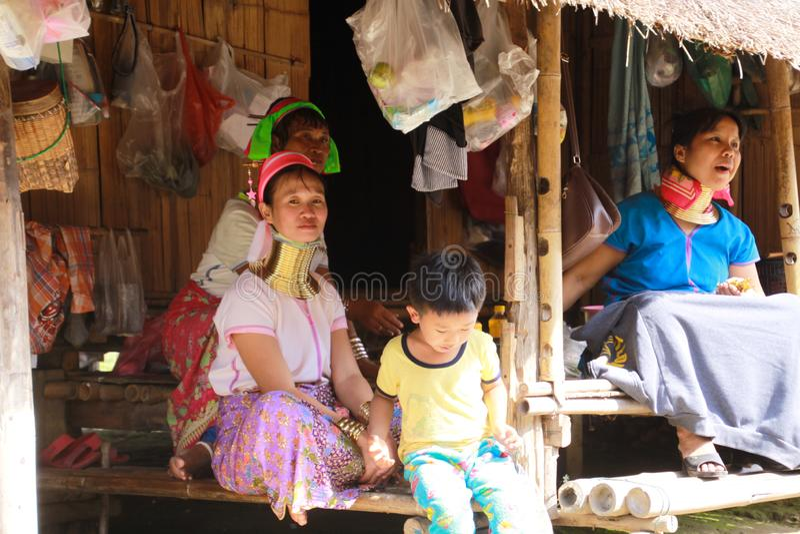 LONGNECK卡伦村庄,泰国- 12月17 2017年:坐在一个竹小屋前面的长的脖子家庭 免版税图库摄影