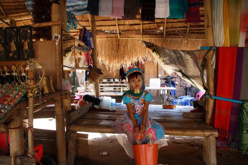LONGNECK卡伦村庄,泰国- 12月17 2017年:年轻长脖子女孩坐偏僻在与茅屋顶的一个小屋 免版税库存照片