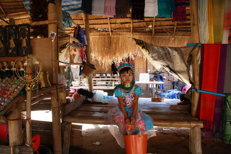 LONGNECK KAREN VILLAGE, THAILAND - DECEMBER 17. 2017: Young Long neck girl sitting lonely in a hut with thatched roof royalty free stock photo