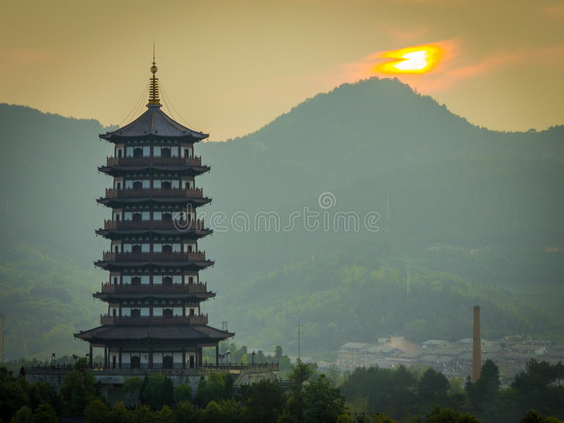 Longquan Pagoda at sunrise. This is a picture of the sun rising over the mountains of Longquan with the pagoda featured prominently in the left hand side of the stock photo
