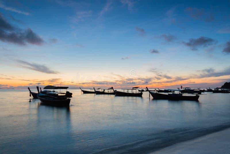 Longs bateaux de longue queue de silhouette d'exposition avec le ciel de lever de soleil en Koh Lipe Island photos libres de droits