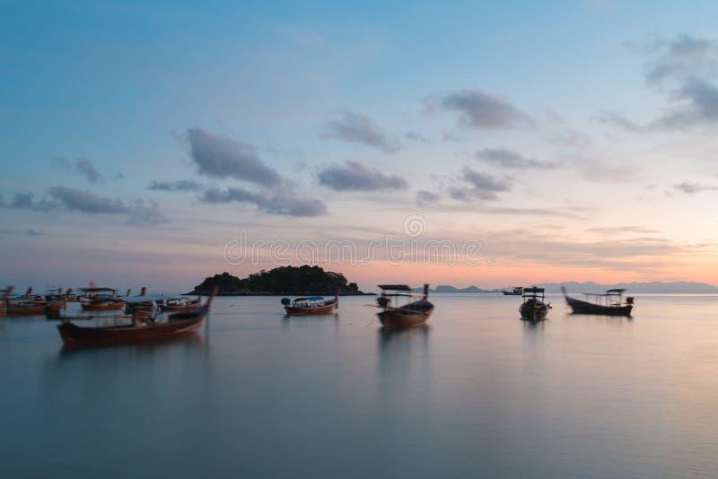 Longs bateaux de longue queue de silhouette d'exposition avec le ciel de lever de soleil en Koh Lipe Island photo stock
