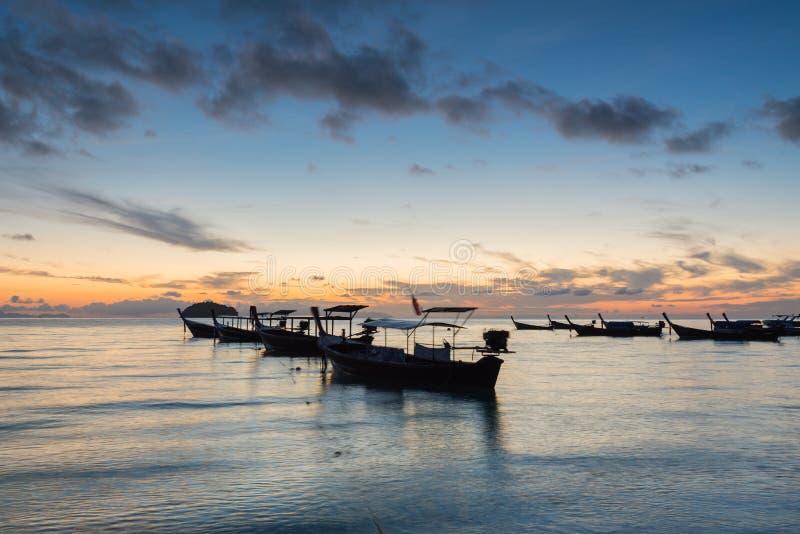 Longs bateaux de longue queue de silhouette d'exposition avec le ciel de lever de soleil en Koh Lipe Island photo libre de droits