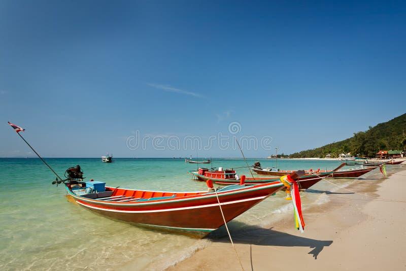 Longs bateaux locaux thaïlandais de conte à la plage sous le ciel bleu clair photographie stock
