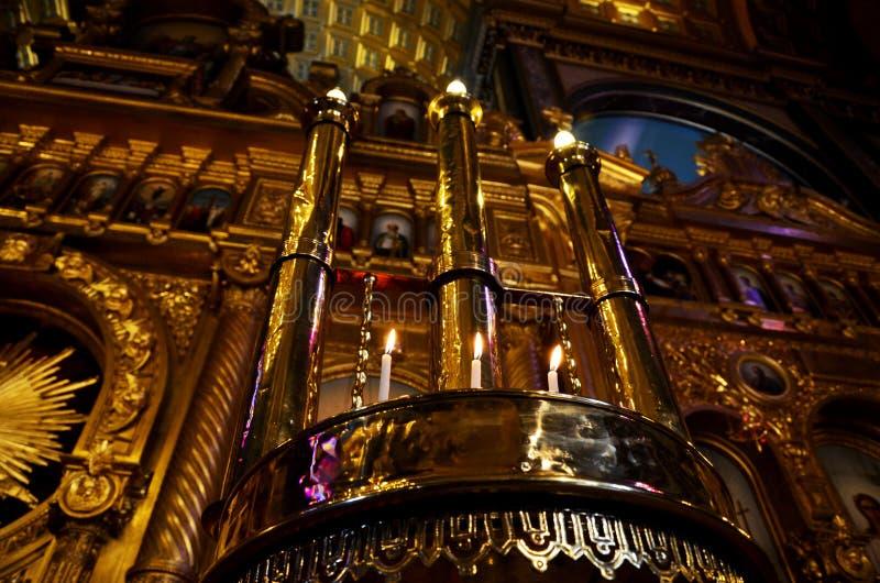 Longs chandeliers en métal comportant les lampes lumineuses et les petites bougies classiques au-dessous de eux dans l'église b photos libres de droits