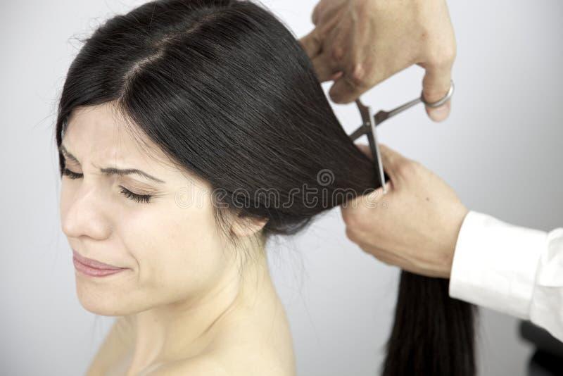 Longs cheveux de moment effrayant coupé par le coiffeur photos stock