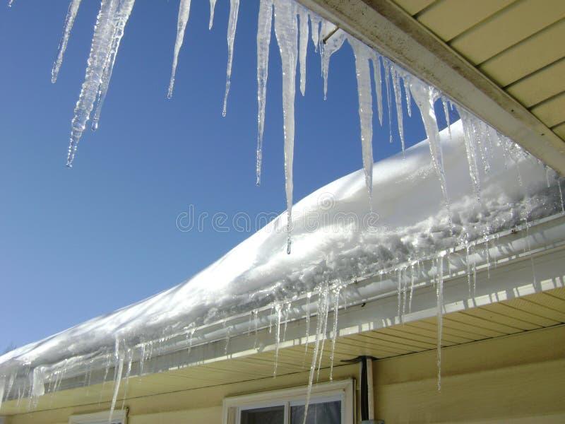 Longs glaçons minces sur le toit par la fenêtre image stock