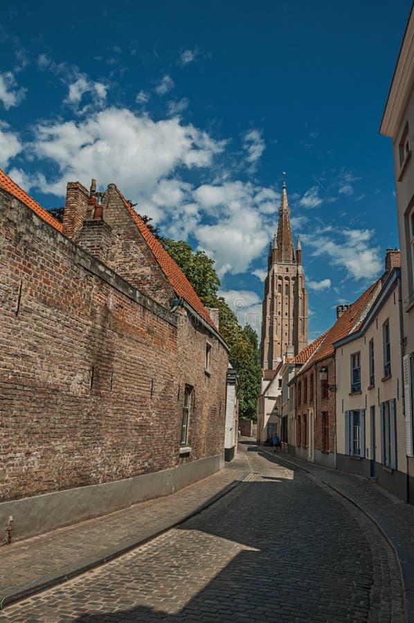 Longs mur de briques, tour et maisons sous le ciel bleu sur la rue de Center's de ville de Bruges images stock