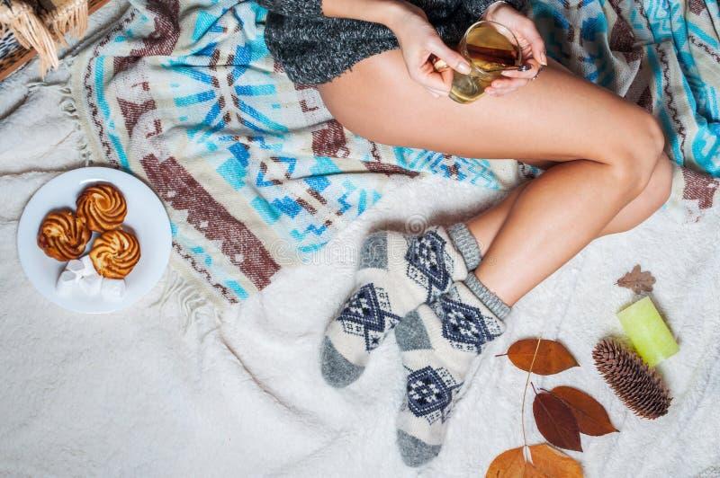 Longs pieds femelles dans les chaussettes de laine chaudes avec la tasse de thé images libres de droits