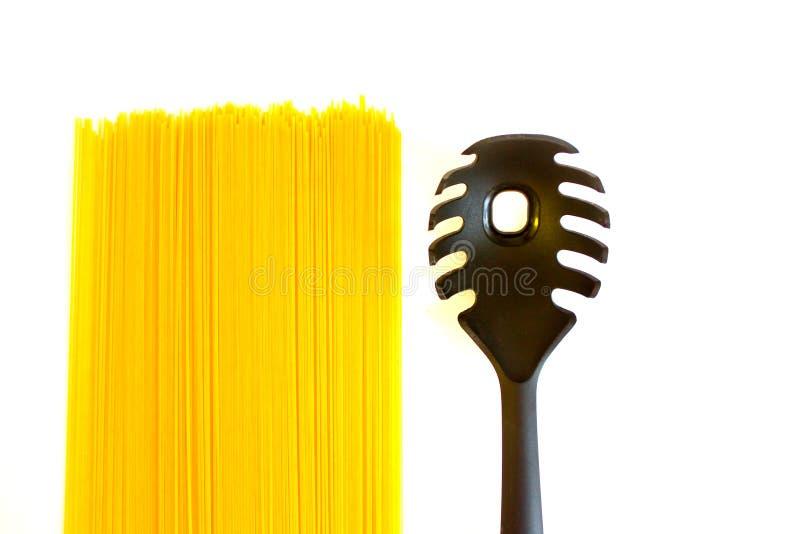 Longs spaghetti jaunes crus et cuillère noire avec le trou d'isolement sur le blanc images stock