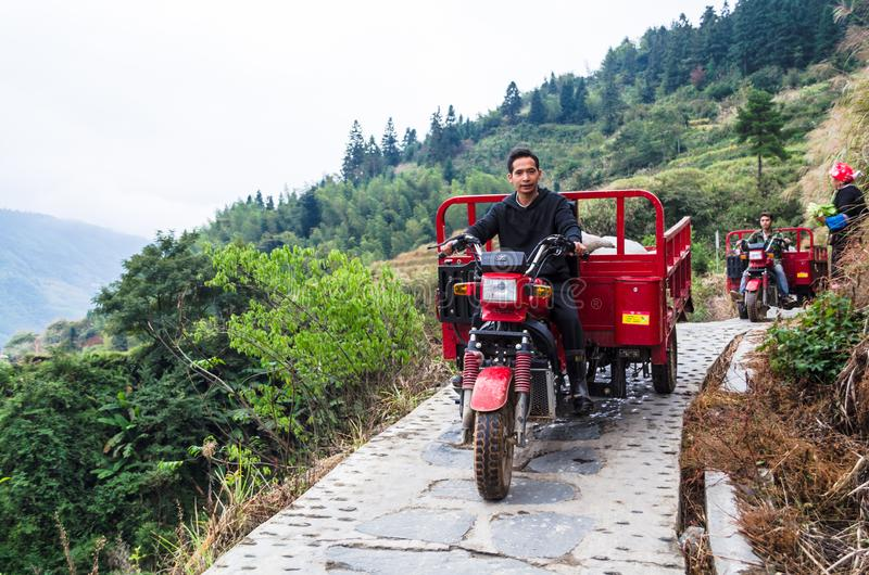 Farmers on motorbikes with trailers, riding along narrow road. LONGSHENG, CHINA - October 19, 2013: Farmers on motorbikes with trailers, riding along a narrow royalty free stock photography