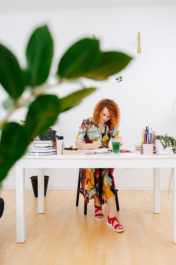 Longshot einer konzentrierten Künstlerin, die hinter einem Arbeitstisch durch eine Pflanze fotografiert wurde stockfotografie